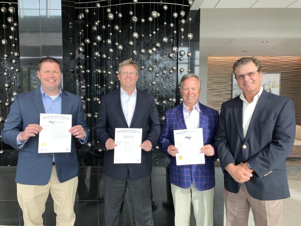 vallit advisors holding up their trademark certificates