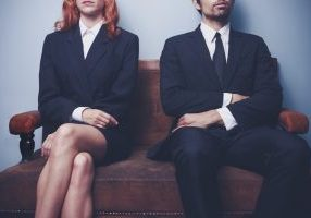 Man and woman waiting to enter a job interview